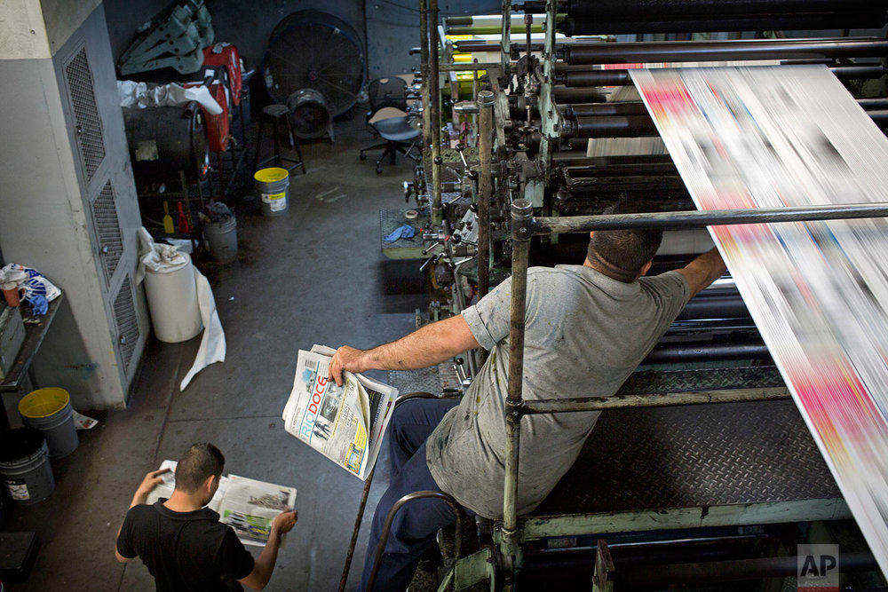 In this late, July 1, 2017 photo, workers print the latest issue of the weekly newspaper Riodoce, in Culiacan, Sinaloa state, Mexico. Journalists at Riodoce persist in covering the violence of Sinaloa, though they are heartbroken after the murder of their paper's co-founder Javier Valdez and the terrain is more treacherous now. (AP Photo/Enric Marti)