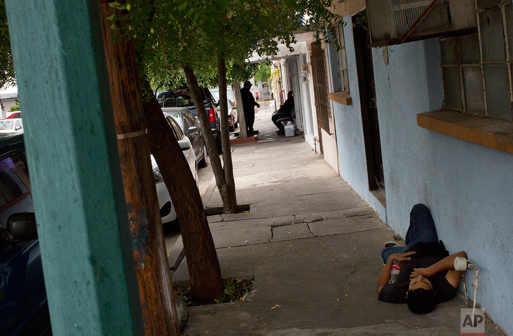 In this June 28, 201 photo, police, behind, sit in the shade as a man rests on the sidewalk outside Riodoce's office in Culiacan, Sinaloa state, Mexico. The police were assigned to this post after the killing of Riodoce reporter Javier Valdez by the state government to guard Riodoce's offices, housed in a apartment building in a middle-class neighborhood of Culiacan. Half-jokingly, some of the reporters wondered whether these officers are among the 50 percent of cops whom the governor himself has said are not trustworthy. (AP Photo/Enric Marti)