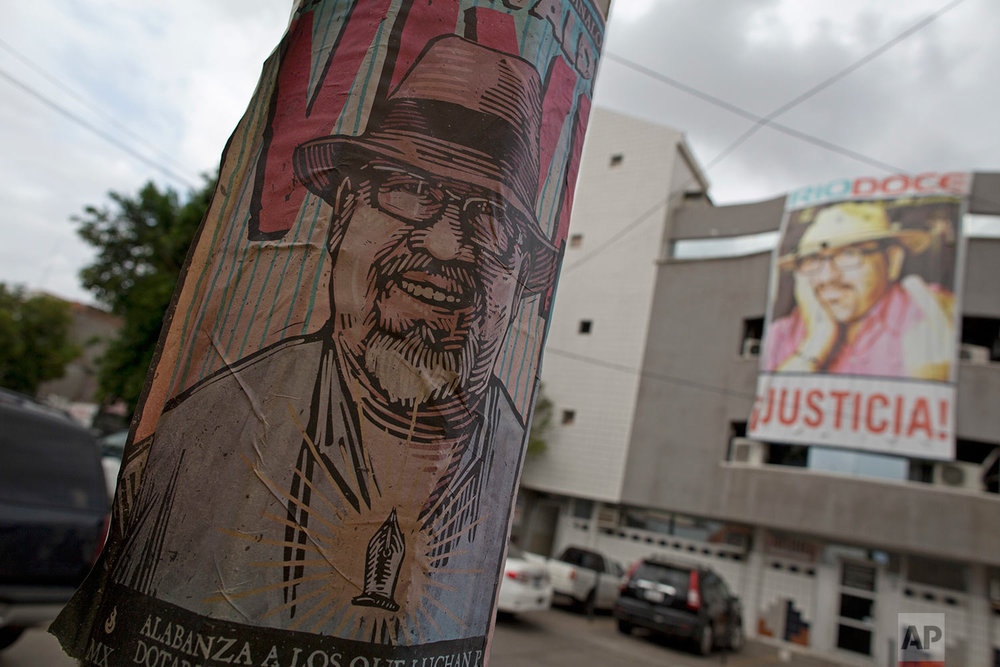In this June 28, 2017, a memorial for slain Riodoce journalist and co-founder Javier Valdez stands at the spot where he was murdered outside his newspaper, behind, in Culiacan, Sinaloa state, Mexico. On the morning of May 15, Valdez left his Riodoce office and managed to drive just a couple of blocks before his red Toyota Corolla was stopped by two men; he was forced out of his car and shot 12 times. (AP Photo/Enric Marti)