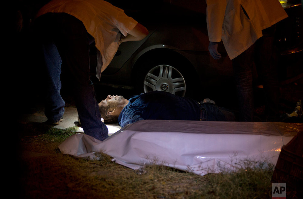 "In this early June 29, 2017 photo, forensics inspect the body of a man who was shot in Culiacan, Sinaloa state, Mexico. Sinaloa is home to the cartel of the same name that was long run by notorious kingpin Joaquin ""El Chapo"" Guzman. Since Guzman's arrest last year and extradition to the United States in January, Sinaloa has been one of the country's bloodiest battlegrounds as rival factions fight to fill the vacuum. (AP Photo/Enric Marti)"