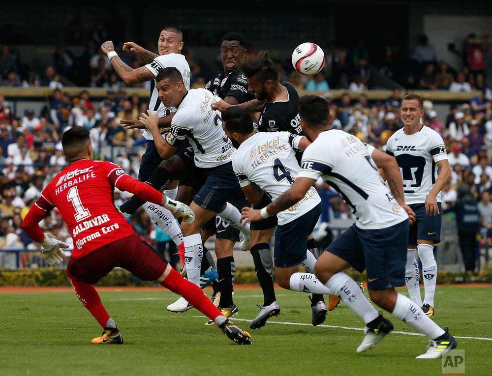 Pumas' Nicolas Castillo, top left, goes for a header against Pachuca's Fabian Murillo, top center, and Robert Herrera, top right, as Pumas' Gerardo Alcoba (3), goalie Alfredo Saldivar (1), Luis Fernando Quintana (4) and Allan Mendoza (5) look on during a Mexico soccer league match in Mexico City, Sunday, July, 23, 2017. Pumas won the match 1-0. ( AP Photo/ Marco Ugarte)