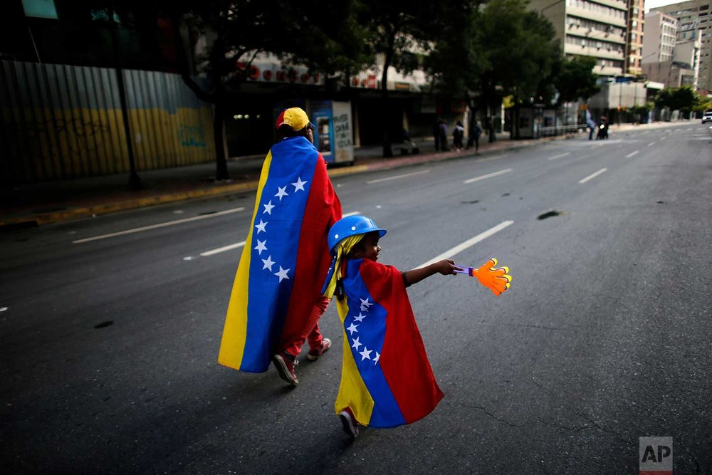 An anti-government demonstrator and her daughter wrapped in the Venezuelan flag walk on an empty street in Caracas, Venezuela, Sunday, July 30, 2017. (AP Photo/Ariana Cubillos)