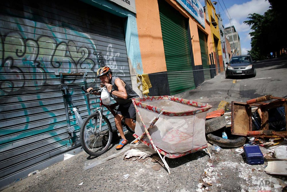 A man who is a resident of Petare neighborhood crosses through a barricade set up by demonstrators to protest against President Nicolas Maduro's plan to rewrite the constitution in Caracas, Venezuela, Saturday, July 29, 2017. (AP Photo/Ariana Cubillos)