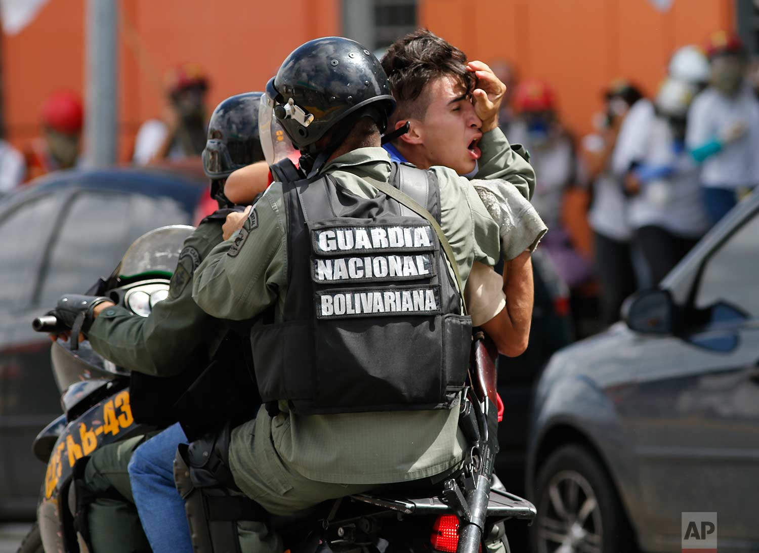 A protester taking part in an anti-government march to the Supreme Court is detained and driven away by Bolivarian National Guard soldiers in Caracas, Venezuela, Thursday, July 6, 2017. (AP Photo/Ariana Cubillos)