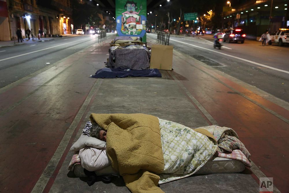 A homeless person sleeps on the sidewalk during a cold night in downtown Sao Paulo, Brazil, Wednesday, July 19, 2017. (AP Photo/Andre Penner)