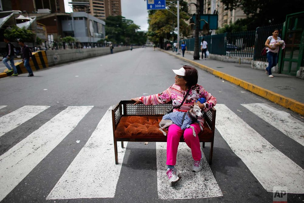An woman sits with her dog on a couch placed in the middle of the street during a call by the opposition to block roads for 10 hours in Caracas, Venezuela, Monday, July 10, 2017. (AP Photo/Ariana Cubillos)