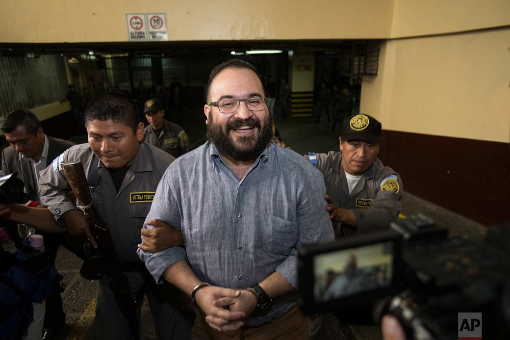 Mexico's former Veracruz state Gov. Javier Duarte smiles as he leaves court in handcuffs after a hearing in Guatemala City, Tuesday, July 4, 2017. (AP Photo/Moises Castillo)