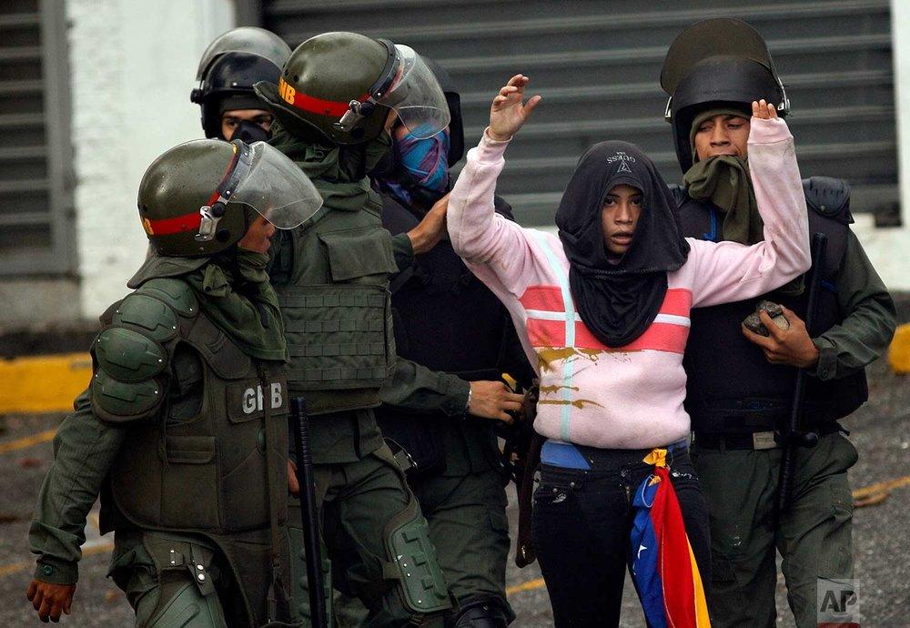 Bolivarian National Guards detain an anti-government demonstrator during clashes in Caracas, Venezuela, Friday, July 28, 2017, two days before the vote to begin the rewriting of Venezuela's constitution. (AP Photo/Ariana Cubillos)