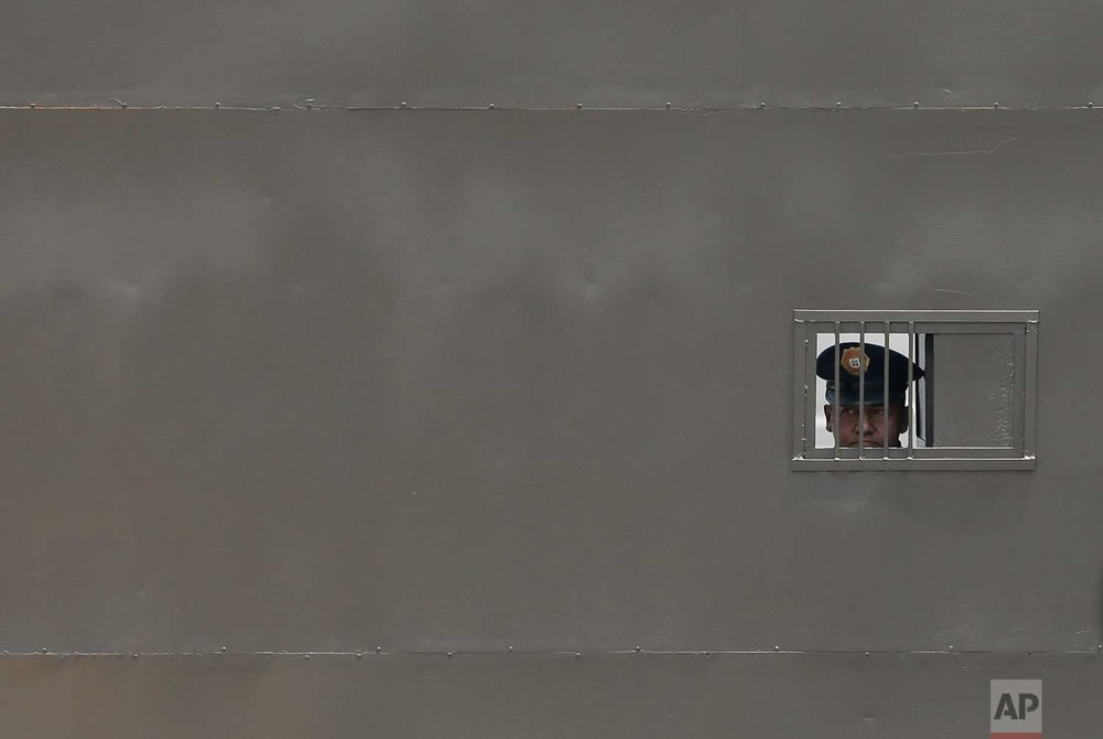 A federal police officer peers out from inside the hangar of the attorney general's office at the Mexico City airport, as former Veracruz State Governor Javier Duarte is processed inside after arriving from Guatemala, Monday, July 17, 2017. (AP Photo/Rebecca Blackwell)