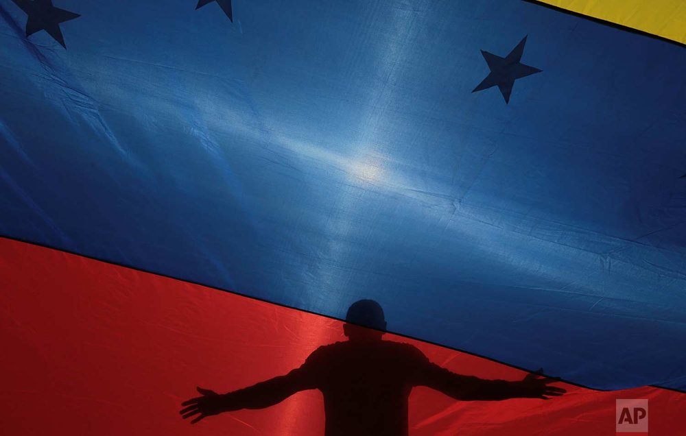 The silhouette of an anti-government protester is seen through a Venezuelan flag during a call by the opposition to block roads for 10 hours in Caracas, Venezuela, Monday, July 10, 2017. (AP Photo/Fernando Llano)