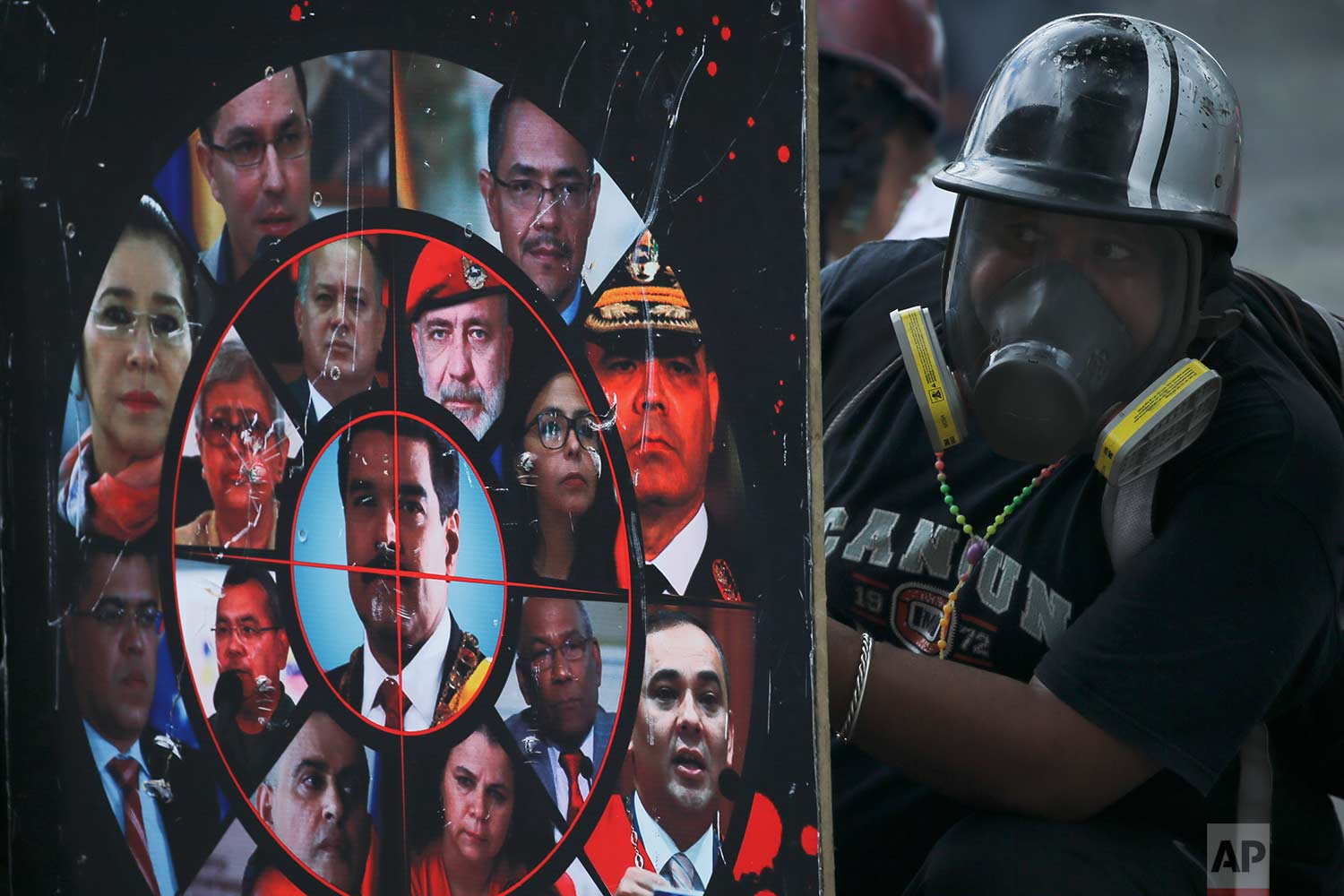 An anti-government protester holds a homemade shield brandished with photos of President Nicolas Maduro, government officials and a gun sight, during clashes with security forces blocking a march to the Supreme Court, in Caracas, Venezuela, Saturday, July 22, 2017. (AP Photo/Fernando Llano)