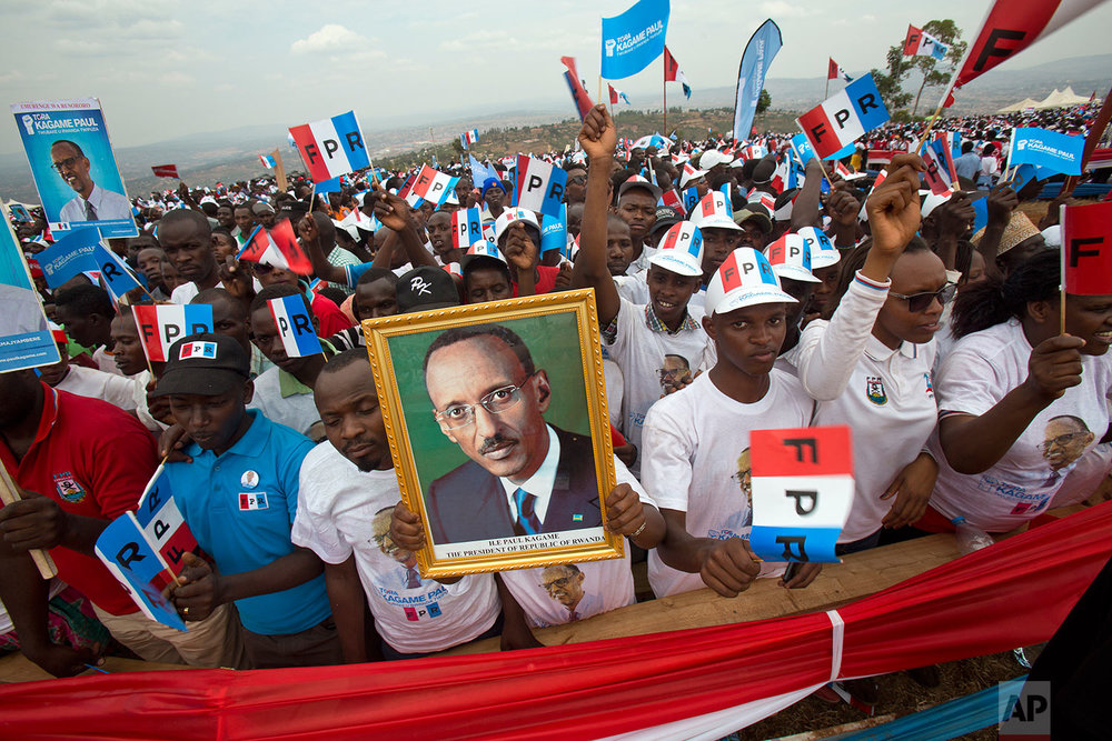 Supporters of Rwanda's President Paul Kagame, portrait center, attend an election campaign rally on the hills overlooking Kigali, Rwanda, Wednesday Aug. 2, 2017. Kagame has been in power since the end of the country's genocide in 1994 and is widely expected to win another term in the Aug. 4 elections after the government earlier this month disqualified all but three candidates. (AP Photo/Jerome Delay)