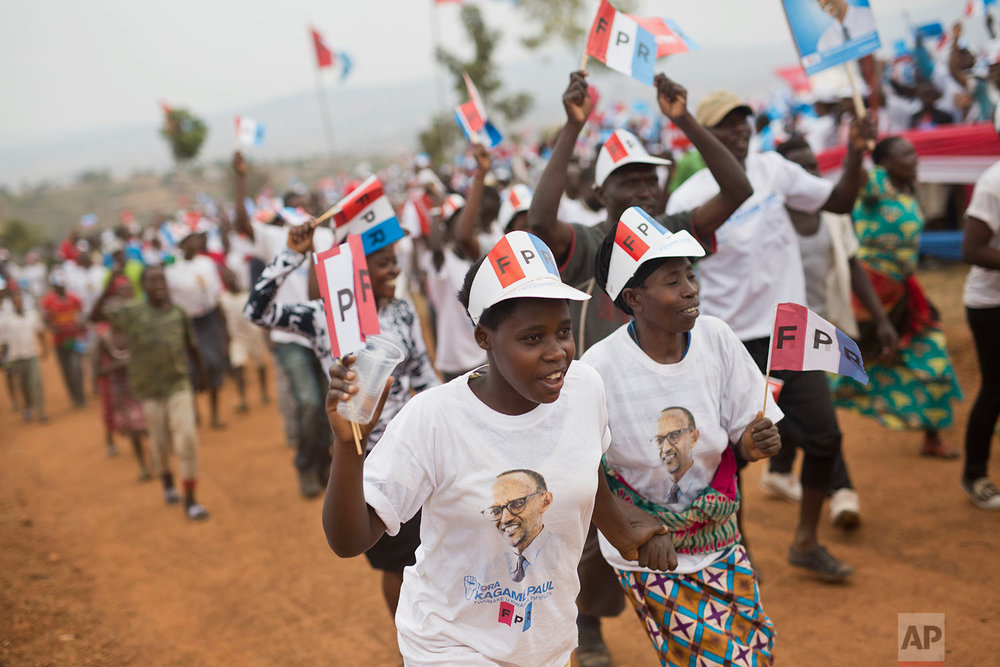 Supporters of Rwanda's President Paul Kagame, center, attend an election campaign rally on the hills overlooking Kigali, Rwanda, Wednesday Aug. 2, 2017. Rwanda's longtime president has already claimed victory in Friday's election. In this strictly run country, Paul Kagame is praised for bringing economic development but criticized for stifling opposition _ and now the constitution allows him to stay in power until 2034. (AP Photo/Jerome Delay)