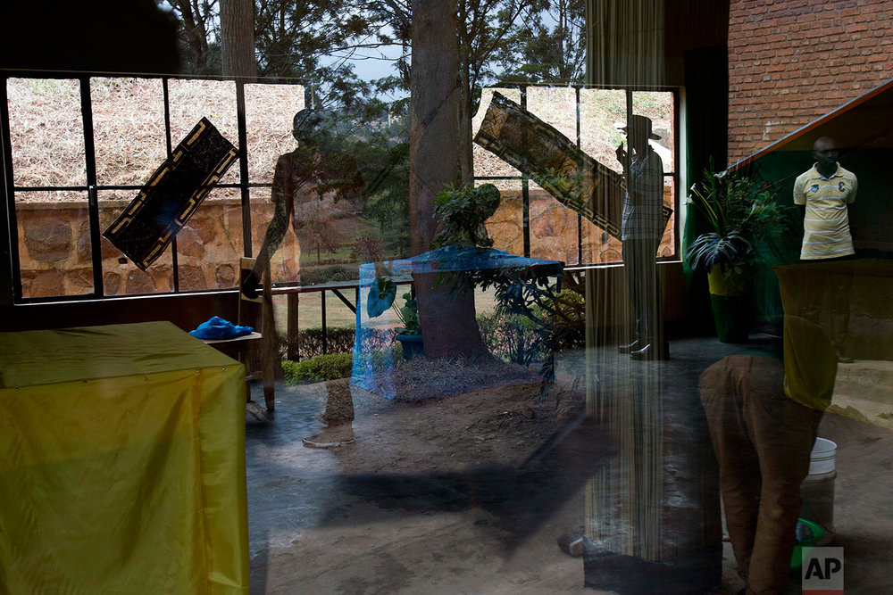 Election volunteers decorate a polling station in Rwanda's capital Kigali, Thursday Aug. 3, 2017, in preparation for the presidential election on Friday in which outgoing president Paul Kagame is widely expected to win another term after the government earlier disqualified all but three candidates. (AP Photo/Jerome Delay)