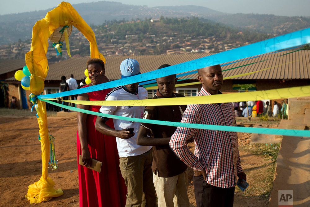 Voters line up to cast their vote at a polling station for the presidential election, Friday Aug. 4, 2017, in the capital Kigali, Rawanda. Incumbent President Paul Kagame is widely expected to win another term after the government disqualified three potential candidates for allegedly failing to fulfill certain requirements, including collecting enough signatures. (AP Photo/Jerome Delay)
