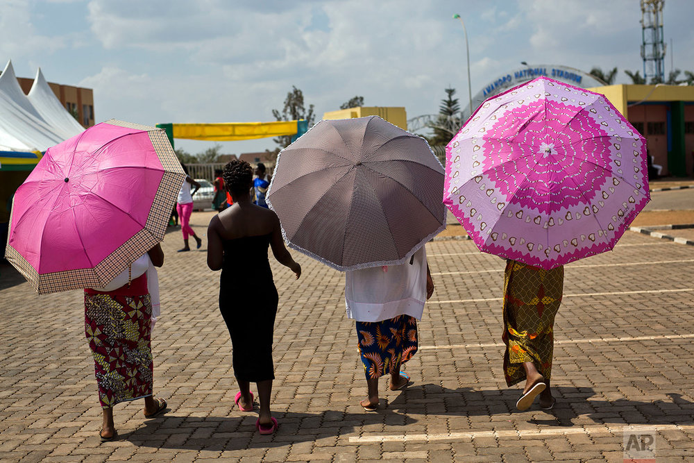 Women leave a polling station in Rwanda's capital Kigali Friday Aug. 4, 2017, after casting their votes in the presidential elections. Rwandans are voting in an election Friday that the country's longtime president is widely expected to win, after the government disqualified all but three candidates.(AP Photo/Jerome Delay)