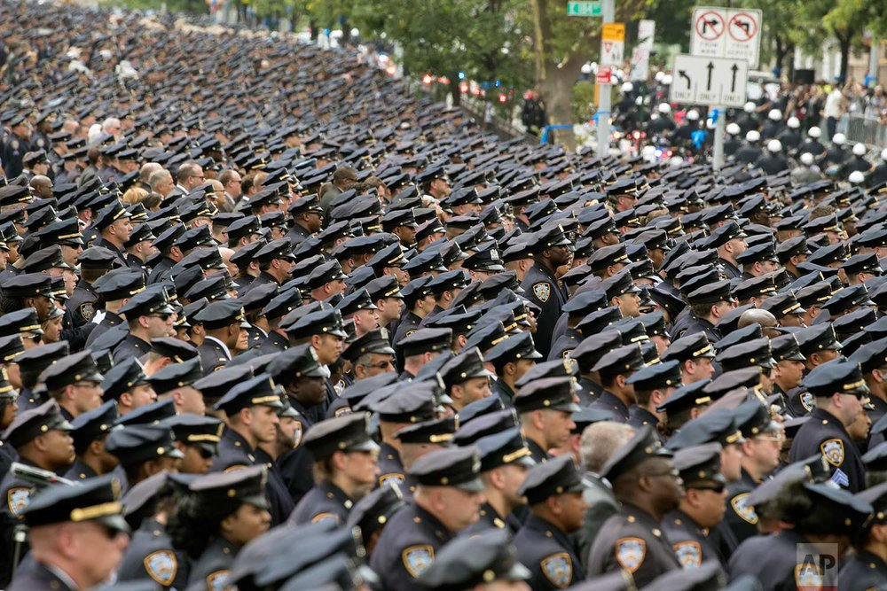Police officers stand at attention as the funeral procession for slain police officer Miosotis Familia leaves at the World Changers Church after her funeral service, Tuesday, July 11, 2017, in the Bronx borough of New York. (AP Photo/Mary Altaffer)