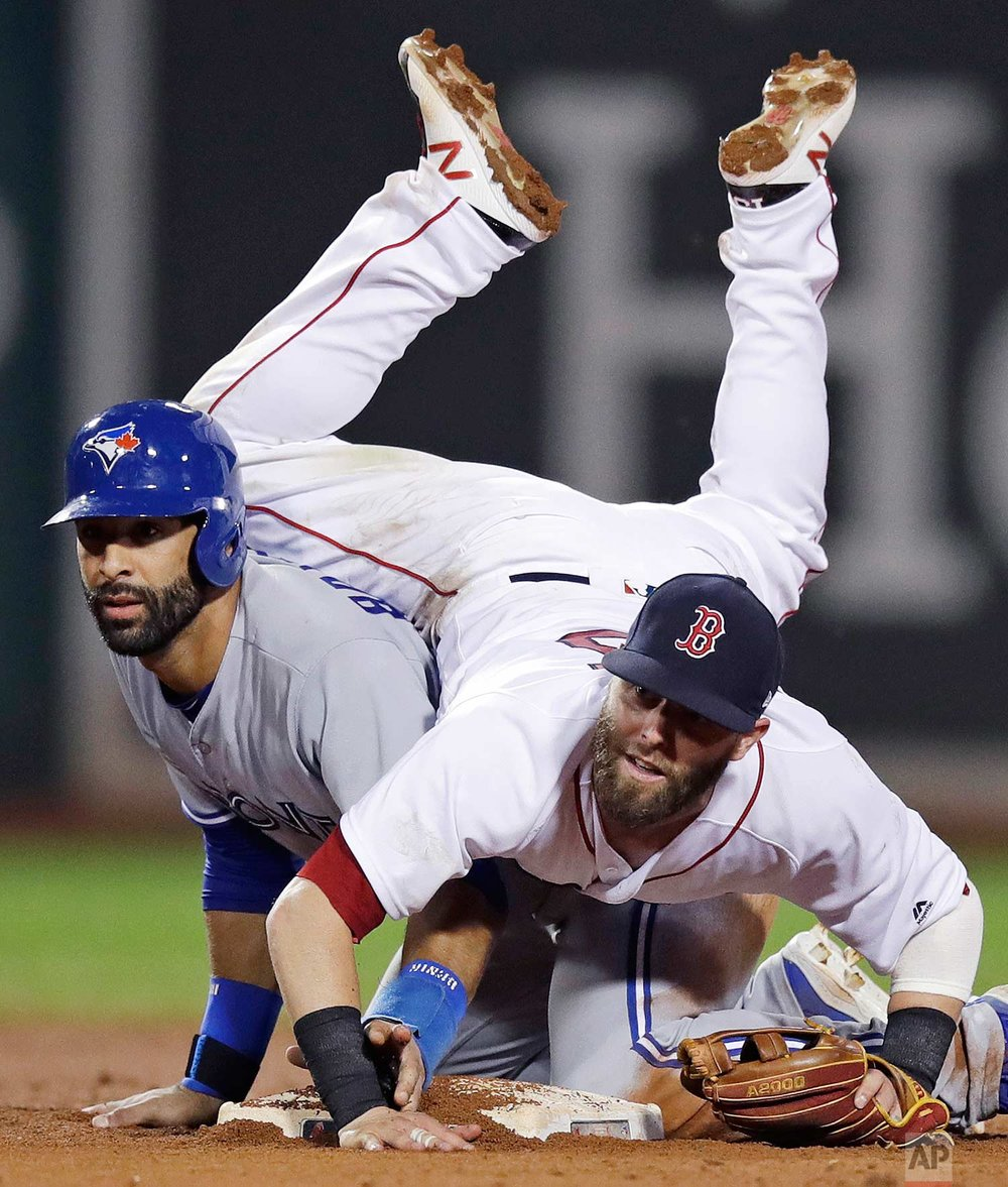 Boston Red Sox second baseman Dustin Pedroia lands on Toronto Blue Jays' Jose Bautista after turning a double play during the 11th inning of a baseball game at Fenway Park in Boston, Tuesday, July 18, 2017. (AP Photo/Charles Krupa)