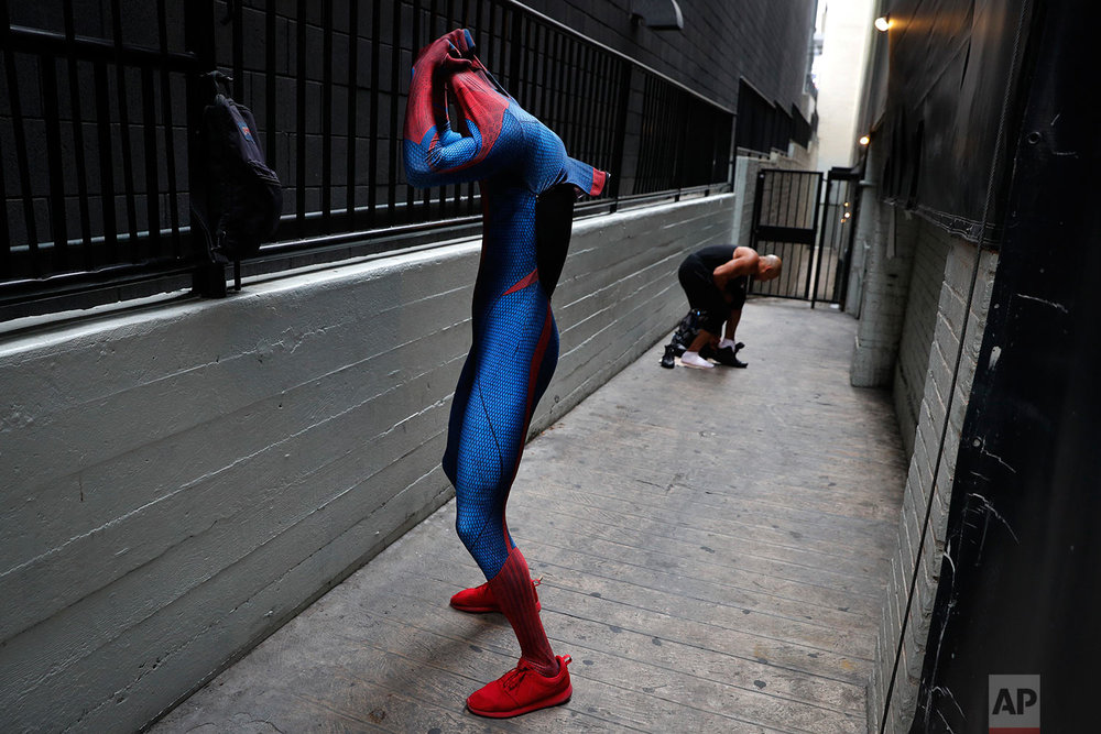 In this Thursday, May 25, 2017 photo, two Spider-Man impersonators, Rashad Rouse, front, and Juan Carlos Banegas, an immigrant from Honduras, change in the alley next to the TCL Chinese Theatre after working on Hollywood Boulevard in Los Angeles. The boulevard is a place of diversity with a cast of superheroes from all over the world including Ukraine, England, Mexico, Germany and Nigeria. (AP Photo/Jae C. Hong)