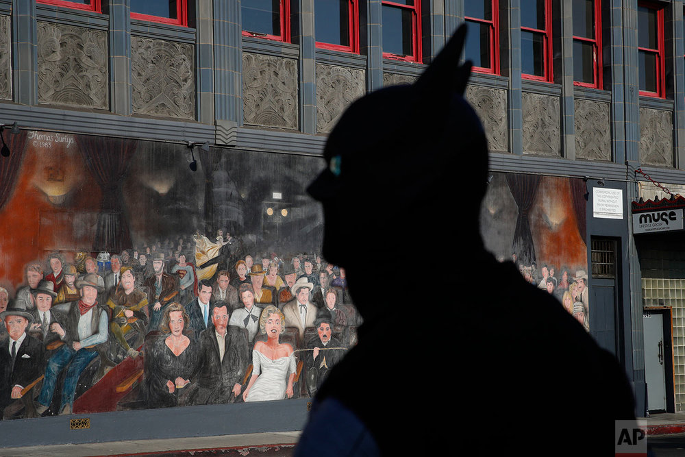 "In this Friday, June 2, 2017 photo, superhero impersonator Omar Budhoo stands in front of Thomas Suriya's mural depicting iconic Hollywood celebrities while waiting for a green light to cross the street in the Hollywood section of Los Angeles. ""My dream is to entertain. My dream has always been to entertain. I'm an actor,"" said the 48-year-old impersonator. ""I'd probably die doing this."" (AP Photo/Jae C. Hong)"