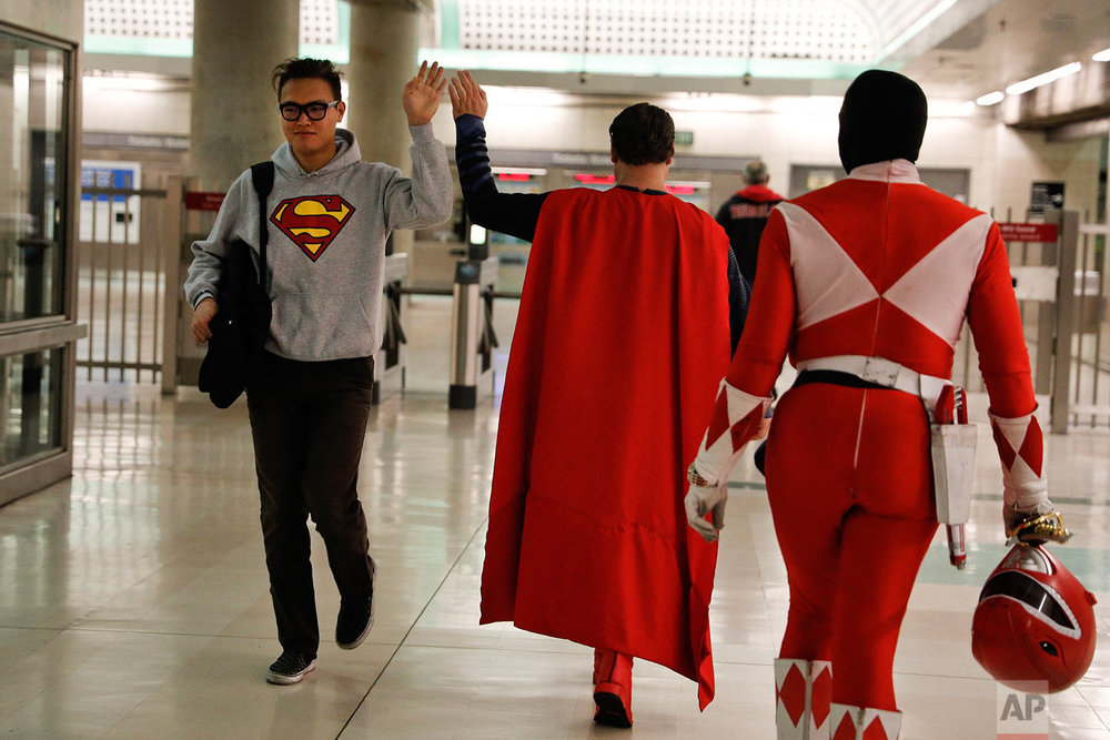 "In this Tuesday, May 16, 2017 photo, Superman impersonator Justin Harrison, center, high-fives a commuter wearing a sweatshirt with a Superman symbol printed on it as he and his roommate, Reginald Jackson, in a Red Power Ranger costume, head back home after working on Hollywood Boulevard, in Los Angeles. ""When I put on any costume of any character, I automatically feel like I am that character,"" said Harrison. (AP Photo/Jae C. Hong)"