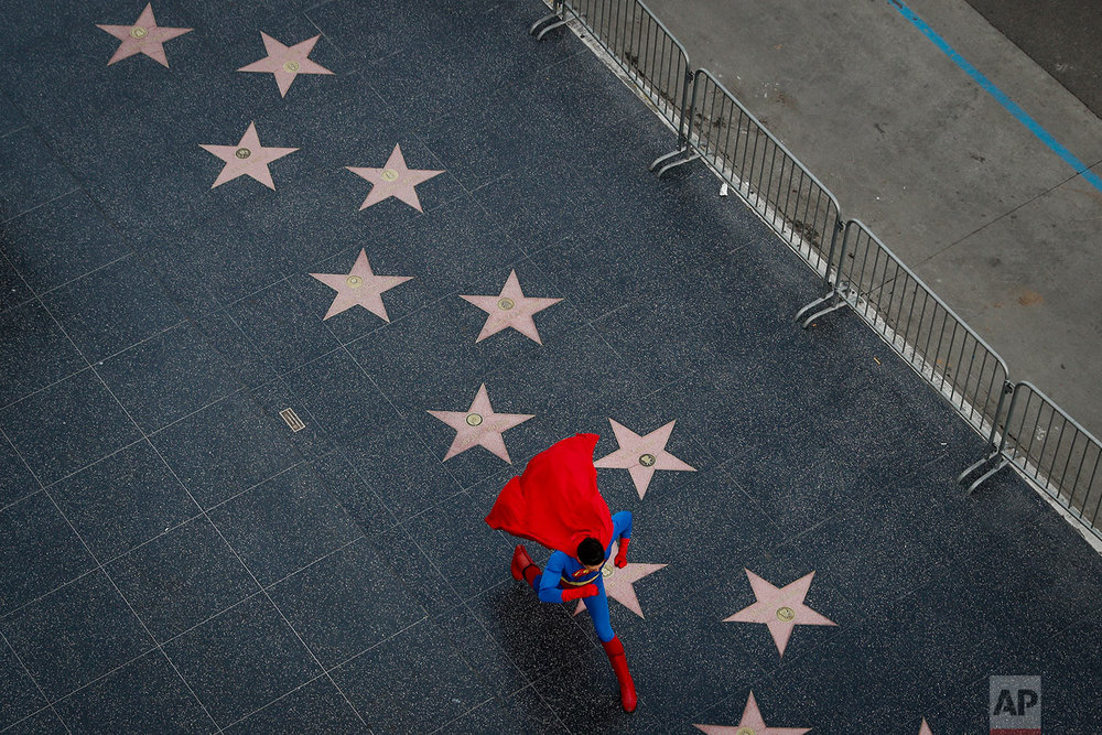 In this Thursday, March 2, 2017 photo, wearing a Superman costume, Toly Shtapenko, of Ukraine, takes a long stride along the Hollywood Walk of Fame to impress tourists, in the Hollywood section of Los Angeles. While the Hollywood we see in movies is a place of glamour and beautiful celebrities, the cast of superheroes filling Hollywood Boulevard is frequently anything but. Many are people struggling to make a buck as they pursue their dream of stardom. (AP Photo/Jae C. Hong)