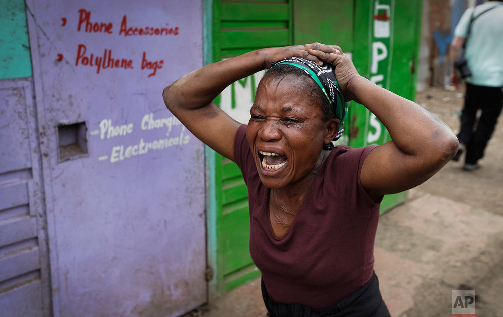 A relative wails near the body of a man who had been shot in the head and who the crowd claimed had been shot by police, in the Mathare area of Nairobi, Kenya ,Wednesday, Aug. 9, 2017. Kenya's election took an ominous turn on Wednesday as violent protests erupted in the capital. (AP Photo/Ben Curtis)