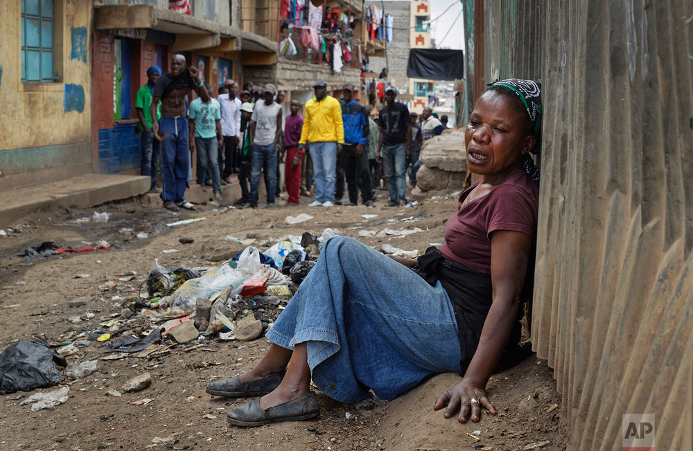 A relative wails on the floor of an alleyway near the body of a man who had been shot in the head and who the crowd claimed had been shot by police, as the angry crowd shouts towards the police, in the Mathare slum of Nairobi, Kenya, Wednesday, Aug. 9, 2017. Kenya's election took an ominous turn on Wednesday as violent protests erupted in the capital. (AP Photo/Ben Curtis)