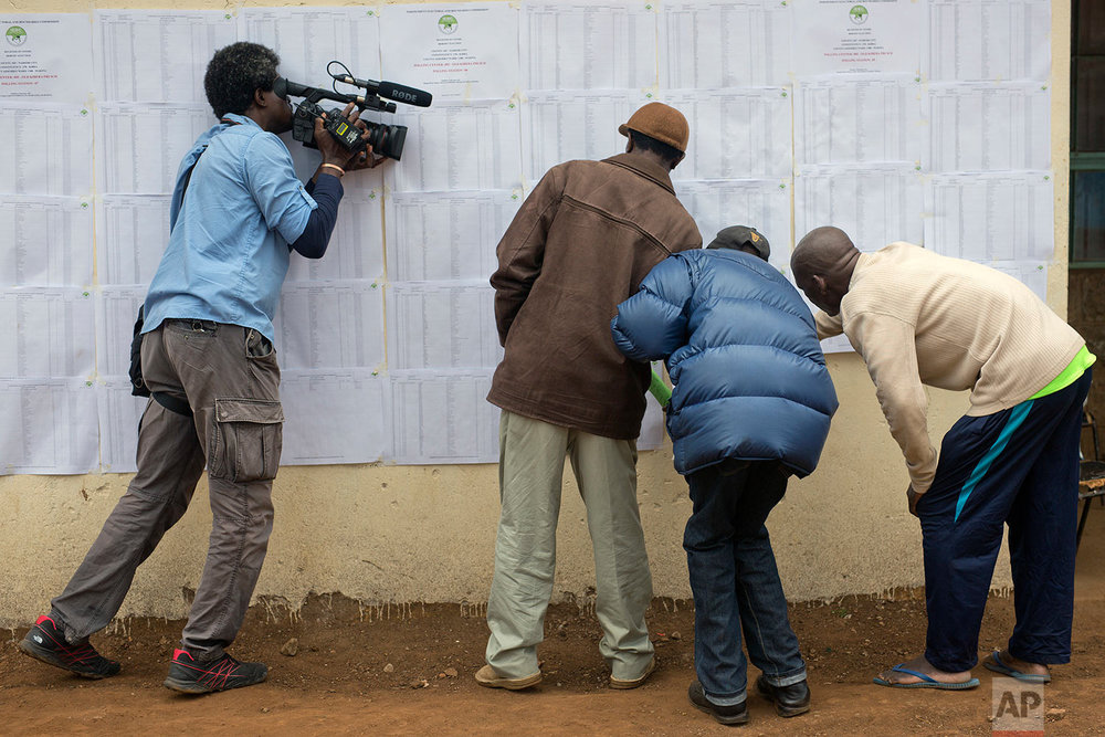 A television cameraman films Kenyans checking if their names are on the electoral lists at a polling station in the Kibera slum in Nairobi, Kenya, Monday, Aug. 7, 2017. Kenyans are due to go to the polls on Aug. 8, to vote in presidential elections after a tightly-fought race between President Uhuru Kenyatta and main opposition leader Raila Odinga. (AP Photo/Jerome Delay)