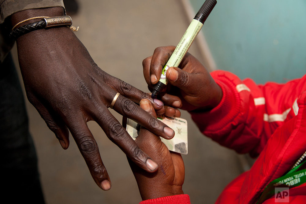 A polling official marks a voter's finger after casting his vote at a polling station in Nairobi, Kenya, Tuesday, Aug. 8, 2017. Kenyans are going to the polls to vote in a general election after a tightly fought presidential race between incumbent President Uhuru Kenyatta and main opposition leader Raila Odinga. (AP Photo/ Sayyid Abdul Azim)