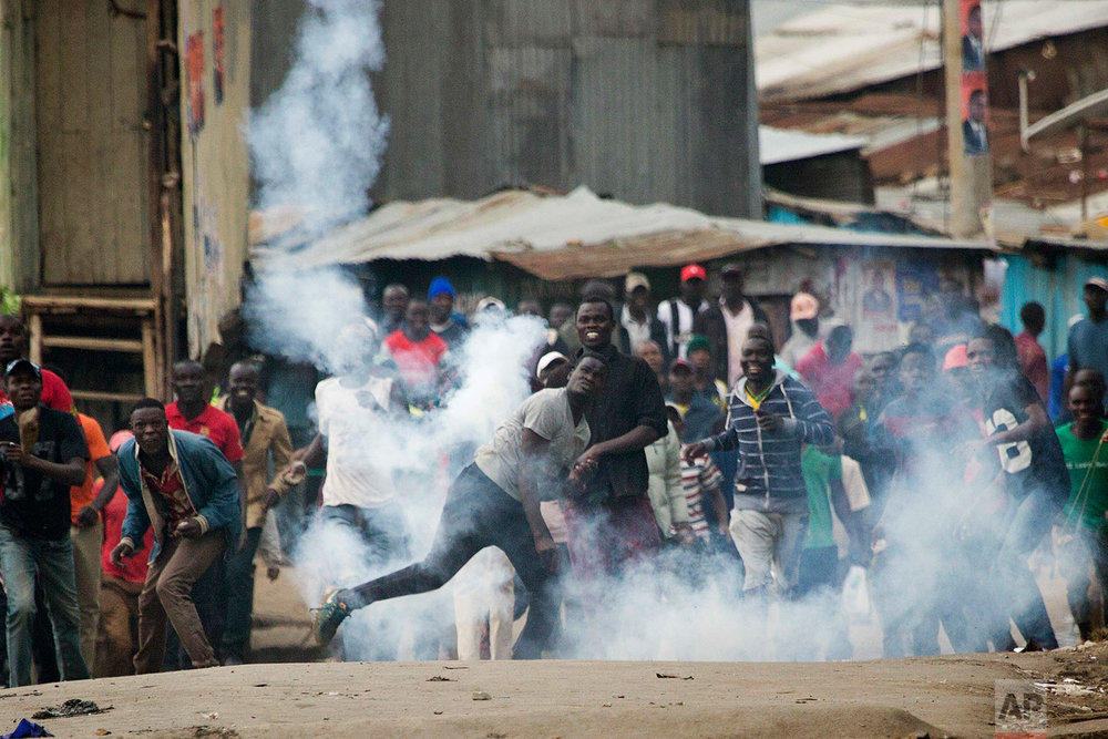 Supporters of Kenyan opposition leader and presidential candidate Raila Odinga throw back a tear gas canister at Kenyan security forces in the Mathare slum of Nairobi, Wednesday, Aug. 9, 2017. Odinga alleges that hackers manipulated the Tuesday election results which appear to show President Uhuru Kenyatta has a wide lead over Odinga. (AP Photo/Jerome Delay)