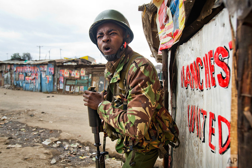 A Kenyan security forces officer shouts before firing a tear gas canister to chase supporters of Kenyan opposition leader and presidential candidate Raila Odinga, who demonstrated in the Mathare area of Nairobi, Wednesday, Aug. 9, 2017. Odinga alleges that hackers manipulated the Tuesday election results which appear to show President Uhuru Kenyatta has a wide lead over Odinga. (AP Photo/Jerome Delay)
