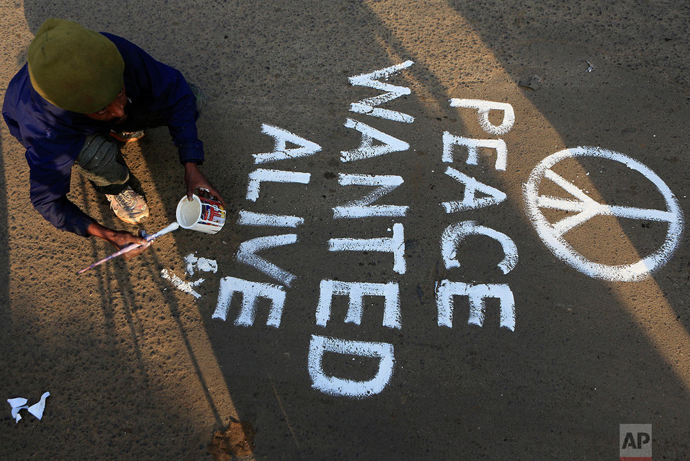 An artist paints a section of the main street into Kibera calling for peace as residents protested in this densely populated suburb in the outskirts of Nairobi, Kenya, Wednesday, Aug. 9, 2017. Kenya's election took an ominous turn on Wednesday as violent protests erupted in the capital. (AP Photo/Noor Khamis)