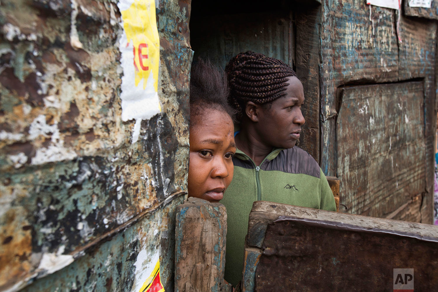 Residents watch Kenyan security forces chase supporters of Kenyan opposition leader and presidential candidate Raila Odinga who demonstrated in the Mathare area of Nairobi, Wednesday, Aug. 9, 2017. Odinga alleges that hackers manipulated the Tuesday election results which appear to show President Uhuru Kenyatta has a wide lead over Odinga. (AP Photo/Jerome Delay)
