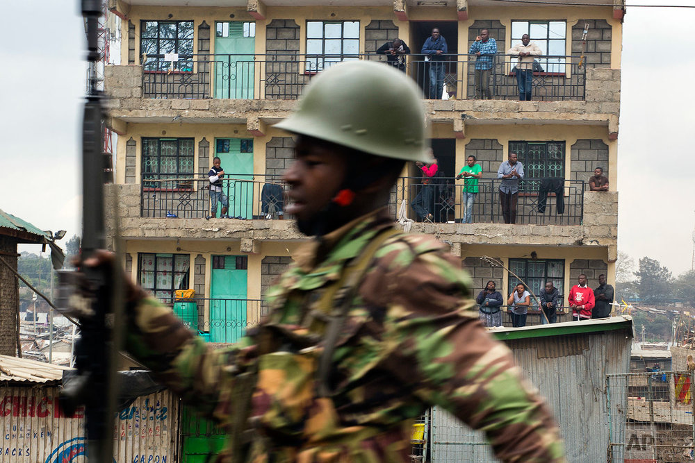 Residents watch from their balconies as Kenyan security forces chase supporters of Kenyan opposition leader and presidential candidate Raila Odinga who demonstrated in the Mathare area of Nairobi, Wednesday, Aug. 9, 2017. Odinga alleges that hackers manipulated the Tuesday election results which appear to show President Uhuru Kenyatta has a wide lead over Odinga. (AP Photo/Jerome Delay)