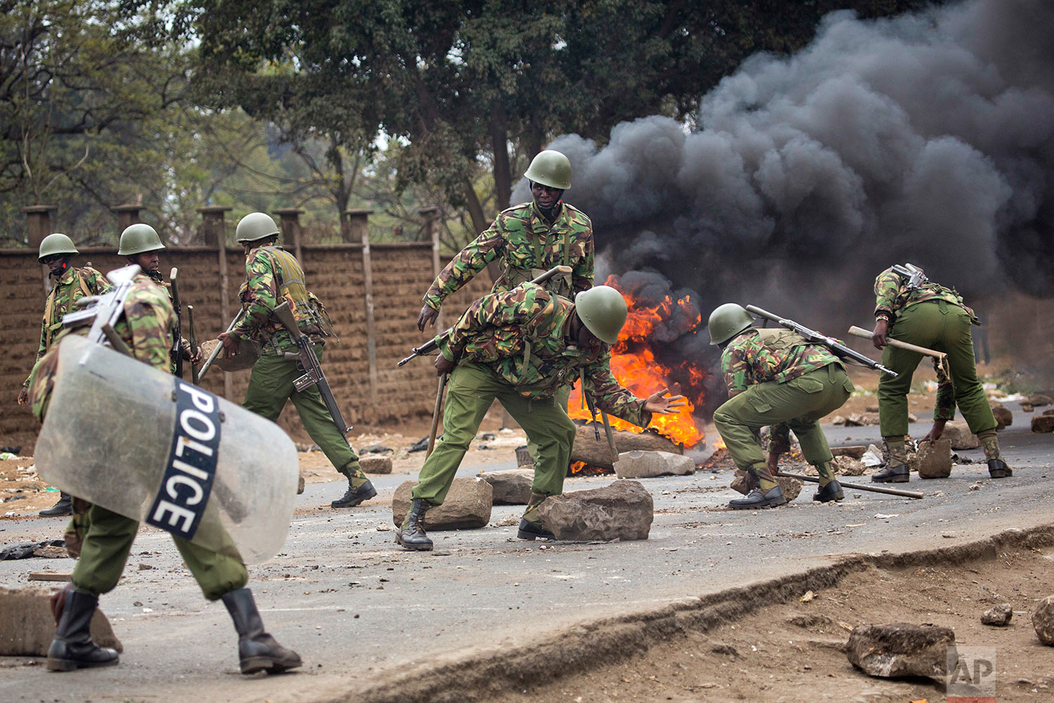Kenyan security forces remove stones from a street blocked by supporters of Kenyan opposition leader and presidential candidate Raila Odinga who demonstrated in the Mathare area of Nairobi, Wednesday , Aug. 9, 2017. Odinga alleges that hackers manipulated the Tuesday election results which appear to show President Uhuru Kenyatta has a wide lead over Odinga. (AP Photo/Jerome Delay)
