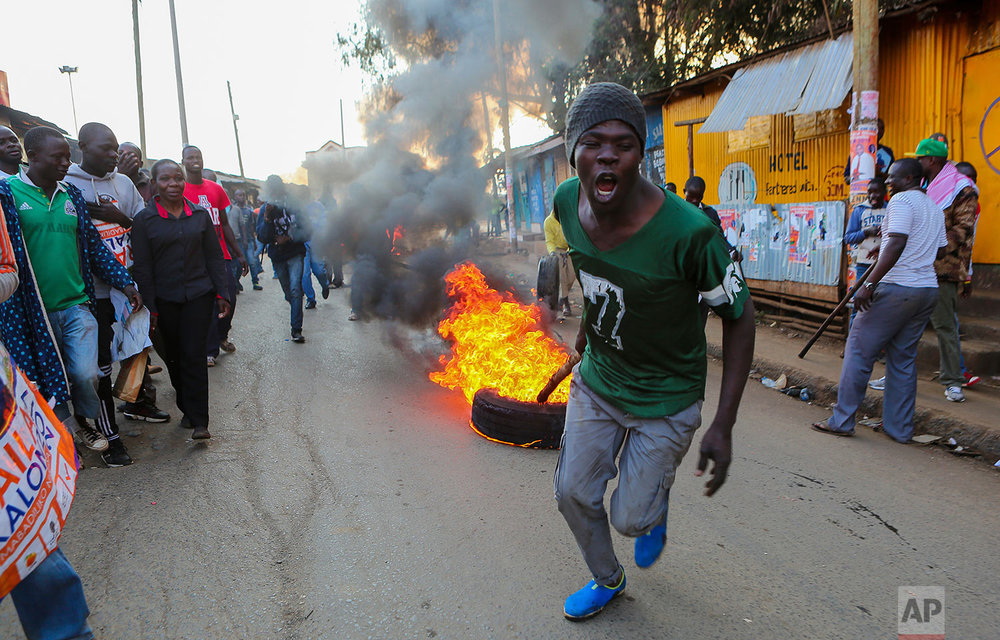 A man pulls a burning tire in Kibera, Nairobi, Kenya, as others block roads with stones to protest in support of Kenyan opposition leader and presidential candidate Raila Odinga, Wednesday, Aug. 9, 2017. Kenya's election took an ominous turn on Wednesday as violent protests erupted in the capital and elsewhere after opposition leader Raila Odinga alleged fraud, saying hackers used the identity of a murdered official to infiltrate the database of the country's election commission and manipulate results. (AP Photo/Brian Inganga)