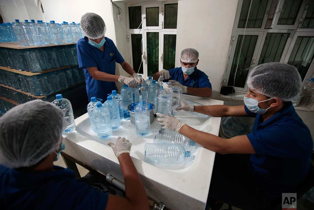 In this photo taken on Saturday, July 8, 2017, workers fill bottles with water at the mineral water refilling station in Sanaa, Yemen. (AP Photo/Hani Mohammed)
