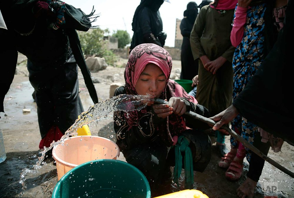 In this photo taken on Wednesday, July 12, 2017, a girl drinks water from a well that is suspected to be contaminated water with the bacterium Vibrio cholera, on the outskirts of Sanaa, Yemen. (AP Photo/Hani Mohammed)