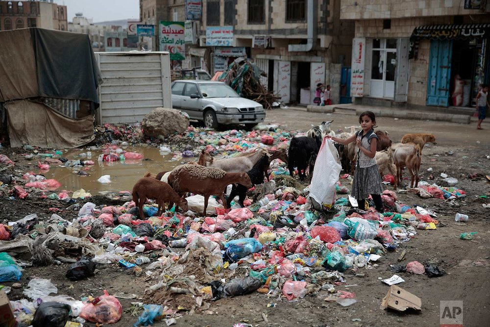 In this photo taken on Wednesday, July 26, 2017, a girl scavenges for recyclable items at a garbage dump in a street in Sanaa, Yemen. (AP Photo/Hani Mohammed)
