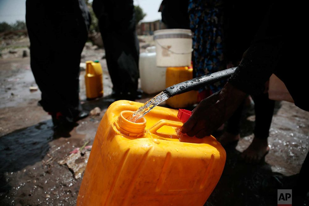 In this photo taken on Wednesday, July 12, 2017, a women fills a bucket with water from a well that alleged to be contaminated water with the bacterium Vibrio cholera, on the outskirts of Sanaa, Yemen. (AP Photo/Hani Mohammed)