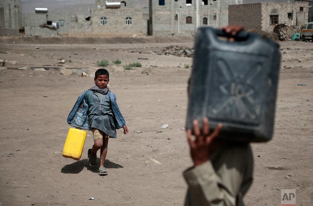 In this photo taken on Wednesday, July 12, 2017, boys carry buckets to fill with water from a well that is alleged to be contaminated water with the bacterium Vibrio cholera, on the outskirts of Sanaa, Yemen. (AP Photo/Hani Mohammed)