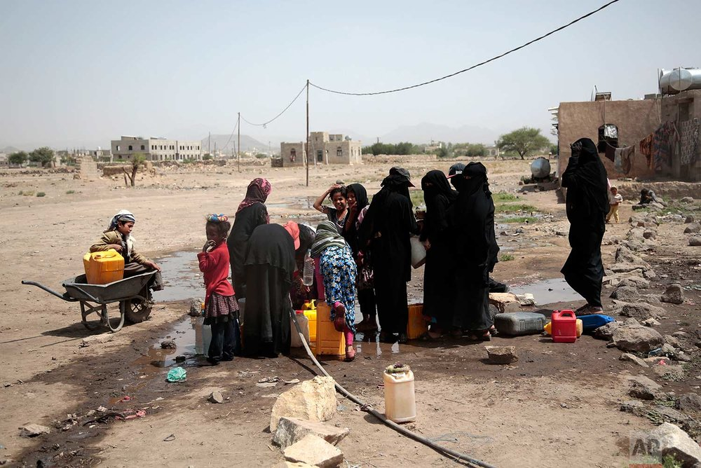 In this photo taken on Wednesday, July 12, 2017, people fill buckets with water from a well that is suspected to be contaminated water with the bacterium Vibrio cholera, on the outskirts of Sanaa, Yemen. (AP Photo/Hani Mohammed)
