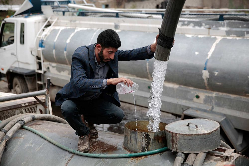 In this photo taken on Wednesday, July 26, 2017, a man adds chlorine solution as he fills a tanker truck  with water from a water tap in Sanaa, Yemen. (AP Photo/Hani Mohammed)