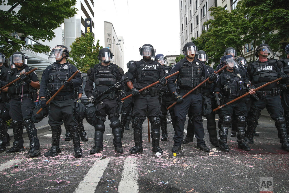 Police stand during a rally Sunday, Aug. 13, 2017, in Seattle. Hundreds of demonstrators and counter-protesters converged in downtown Seattle one day after violent clashes in Charlottesville, Va. (Grant Hindsley/seattlepi.com via AP)