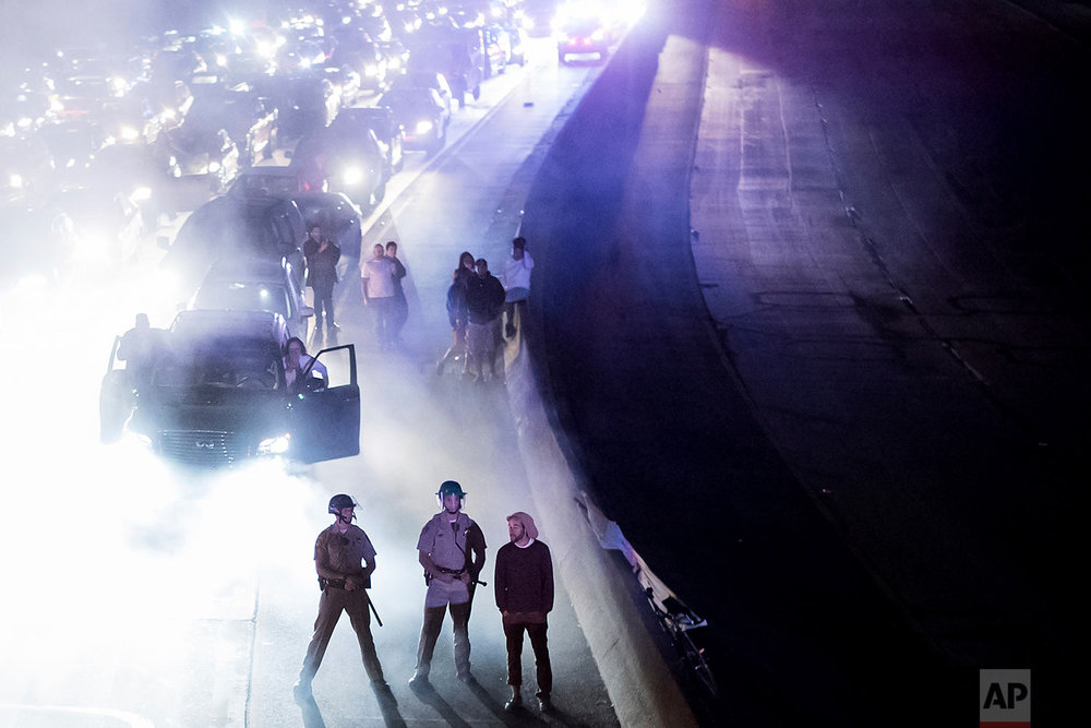 Police officers stand watch as protesters against racism block traffic on both directions of Interstate 580 in Oakland, Calif., Saturday, Aug. 12, 2017. (AP Photo/Noah Berger)