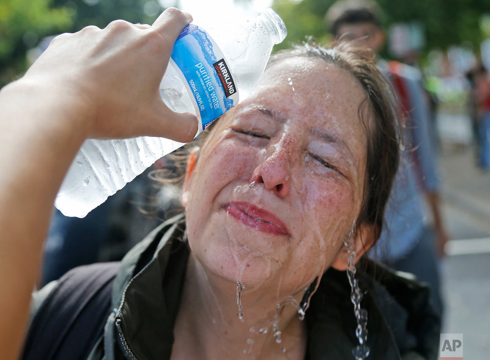 A counter demonstrator gets a splash of water after being hit by pepper spray at the entrance to Lee Park in Charlottesville, Va., Saturday, Aug. 12, 2017. Gov. Terry McAuliffe declared a state of emergency and police dressed in riot gear ordered people to disperse after chaotic violent clashes between white nationalists and counter protestors. (AP Photo/Steve Helber)