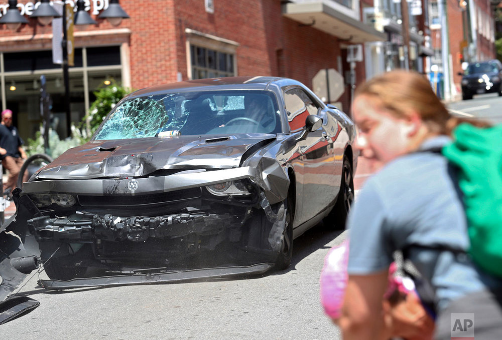 A vehicle reverses after driving into a group of protesters demonstrating against a white nationalist rally in Charlottesville, Va., Saturday, Aug. 12, 2017. (Ryan M. Kelly/The Daily Progress via AP)