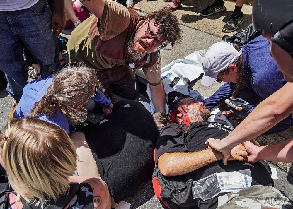 In this Saturday, Aug. 12, 2017 photo, responders work with victims at the scene where a man identified by police as James Alex Fields Jr., plowed a car into a crowd of people who had gathered to protest a white supremacist rally earlier in the day, in Charlottesville, Va. Police charged Fields with second-degree murder and other counts. (Go Nakamura via AP)