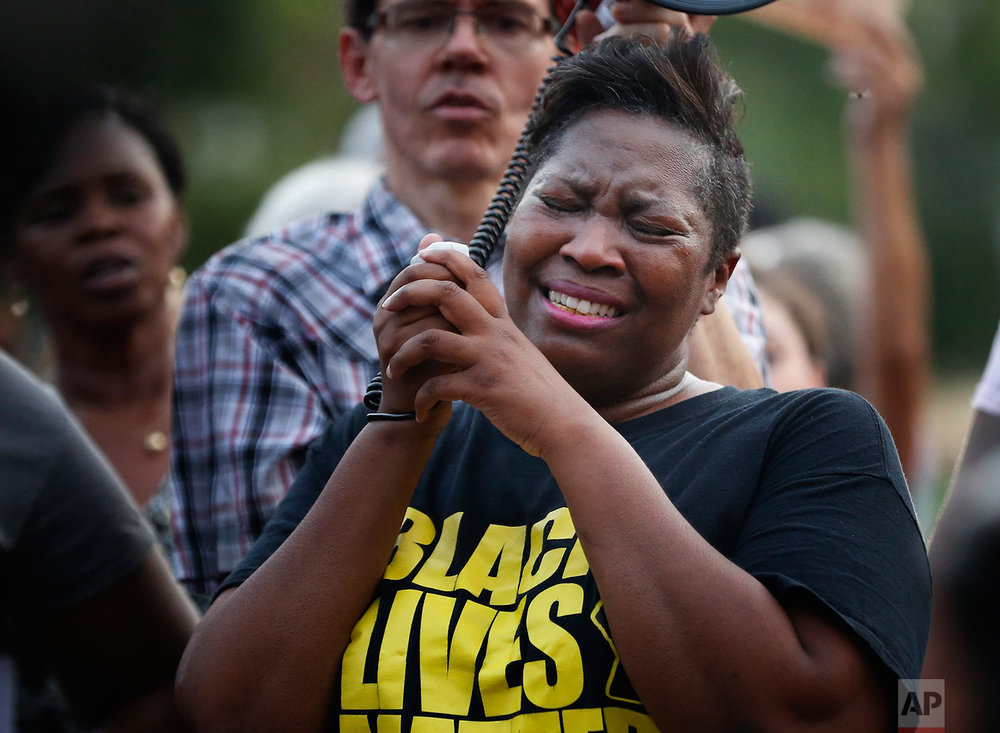 Cara McClure, of Birmingham, Ala, cries during a solidarity gathering Sunday, Aug. 13, 2017, in Birmingham for the victims in Charlottesville, Va. (AP Photo/Brynn Anderson)